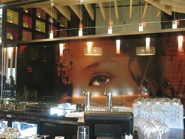 dark colored window graphics of woman with eye in bar