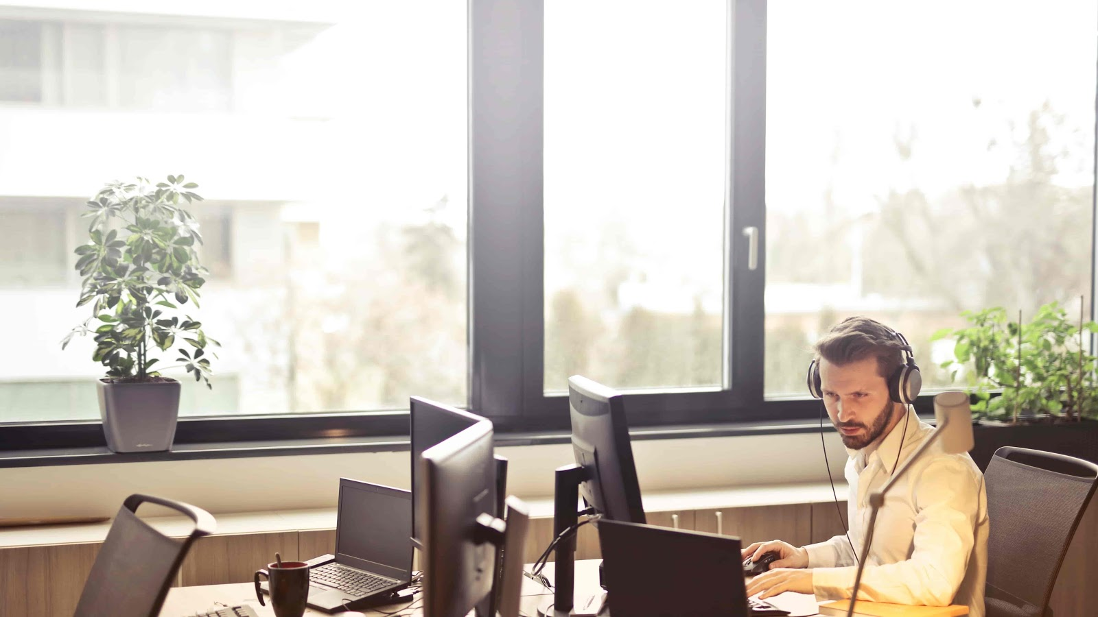 man working at a desk next to large window
