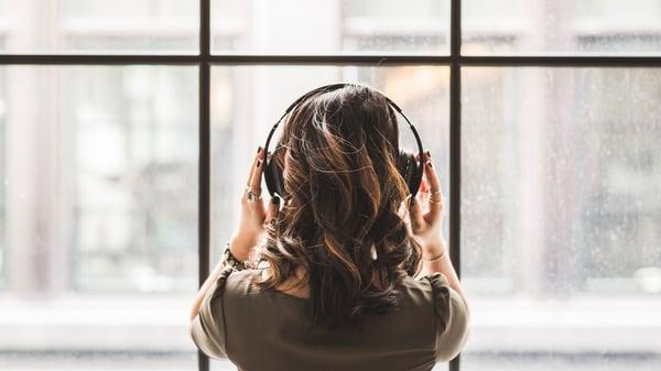 woman wearing headphone in front of a window